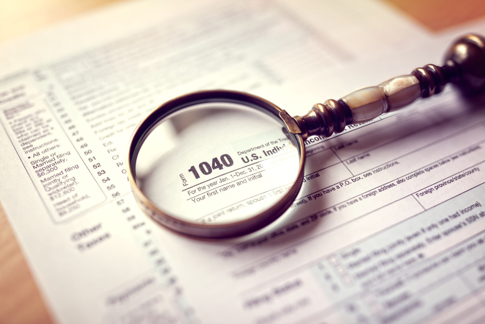 Income tax 1040 us individual tax return form and magnifying glass